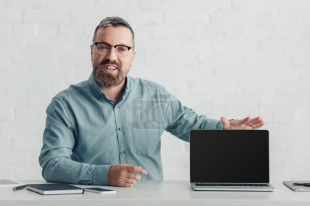 handsome businessman in shirt holding laptop with copy space