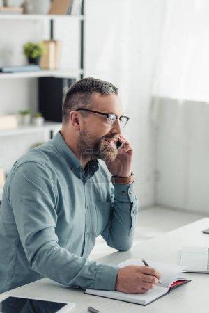 Photo pour Homme d'affaires beau dans la chemise et les glaces parlant sur le smartphone et le stylo de fixation - image libre de droit