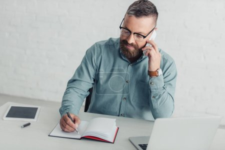 handsome businessman in shirt and glasses talking on smartphone and holding pen