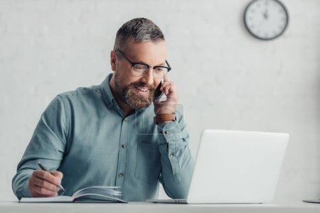handsome businessman in shirt and glasses talking on smartphone holding pen