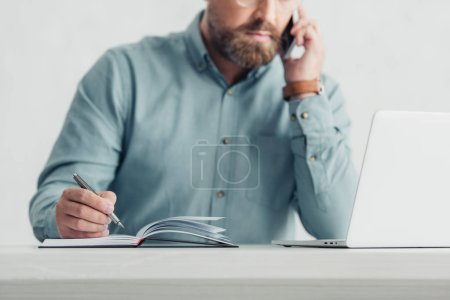 Photo for Cropped view of businessman in shirt talking on smartphone and holding pen - Royalty Free Image