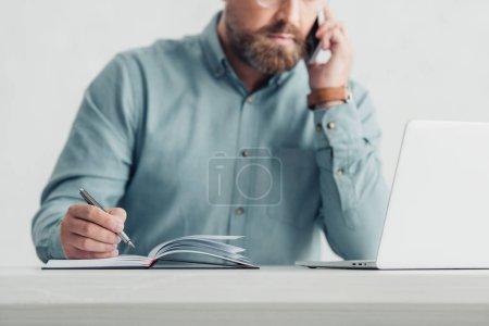 abgeschnittene Ansicht eines Geschäftsmannes im Hemd, der mit Smartphone und Stift spricht