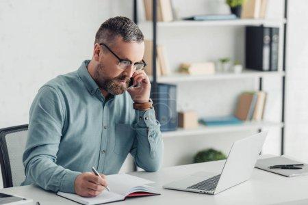 Photo pour Bel homme d'affaires en chemise et lunettes parlant sur smartphone - image libre de droit