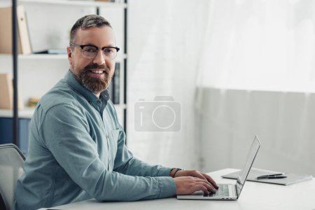 handsome businessman in shirt and glasses using laptop and looking at camera