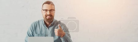 Photo pour Panoramic shot of handsome businessman in shirt and glasses looking at camera and showing thumb up - image libre de droit