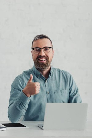 Photo for Handsome businessman in shirt and glasses looking at camera and showing thumb up - Royalty Free Image