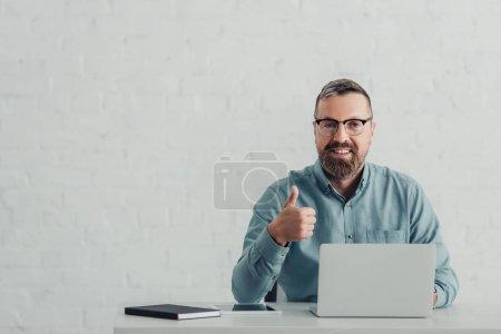 Photo pour Bel homme d'affaires en chemise et lunettes regardant la caméra et montrant pouce vers le haut - image libre de droit