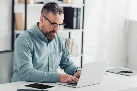 Photo pour Homme d'affaires beau dans la chemise et les glaces utilisant l'ordinateur portatif dans le bureau - image libre de droit