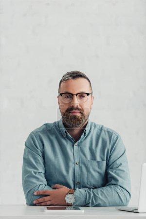 Photo pour Bel homme d'affaires en chemise et lunettes regardant la caméra dans le bureau - image libre de droit