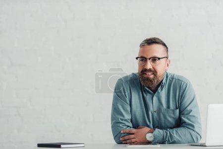 Photo pour Bel homme d'affaires en chemise et lunettes regardant loin dans le bureau - image libre de droit