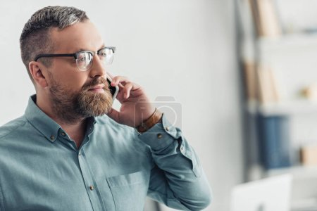 Photo for Handsome businessman in shirt and glasses talking on smartphone in office - Royalty Free Image