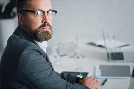 handsome businessman in formal wear and glasses looking at camera in office