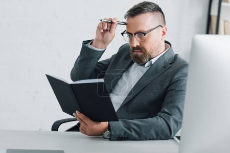 Photo for Handsome businessman in formal wear and glasses holding pen and notebook in office - Royalty Free Image