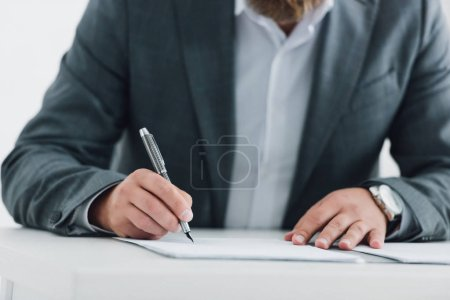 Photo for Cropped view of businessman in formal wear writing with pen in office - Royalty Free Image