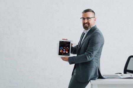 Photo pour Beau homme d'affaires dans l'usure formelle tenant la tablette numérique avec des diagrammes et des graphiques web - image libre de droit
