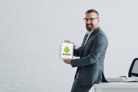 Photo pour Kiev, Ukraine - 27 août 2019: beau homme d'affaires en tenue formelle tenant tablette numérique avec logo Android - image libre de droit
