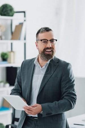 handsome businessman in formal wear and glasses using digital tablet in office