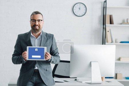 Photo pour KYIV, UKRAINE - 27 AOÛT 2019 : bel homme d'affaires en tenue formelle tablette numérique avec site facebook - image libre de droit