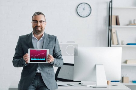 Photo for Handsome businessman in formal wear holding digital tablet with graphs on screen - Royalty Free Image