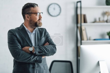 Photo for Handsome businessman in formal wear with crossed arms looking away - Royalty Free Image