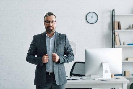 schöner Geschäftsmann in formeller Kleidung, der in seiner Wohnung in die Kamera blickt
