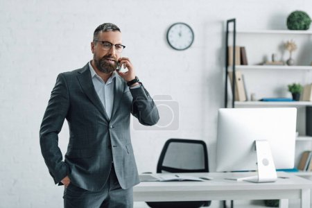 Photo for Handsome businessman in formal wear and glasses talking on smartphone - Royalty Free Image