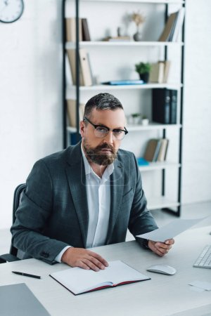 Photo for Handsome businessman in formal wear and glasses doing paperwork - Royalty Free Image