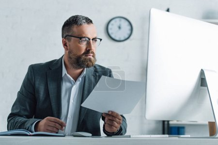 handsome businessman in formal wear and glasses doing paperwork