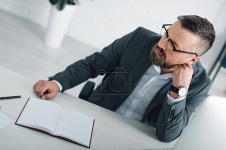 Photo pour Bel homme d'affaires dans l'usure formelle et les lunettes regardant loin dans le bureau - image libre de droit