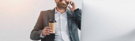 Panoramaaufnahme eines Geschäftsmannes in offizieller Kleidung, der mit Smartphone spricht und Pappbecher hält