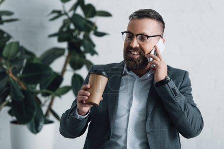 Photo pour Bel homme d'affaires en tenue formelle parlant sur smartphone et tenant tasse en papier - image libre de droit