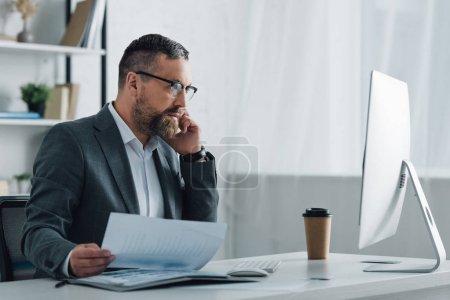 Foto de Guapo hombre de negocios en ropa formal hablando en el teléfono inteligente y la celebración de documento - Imagen libre de derechos