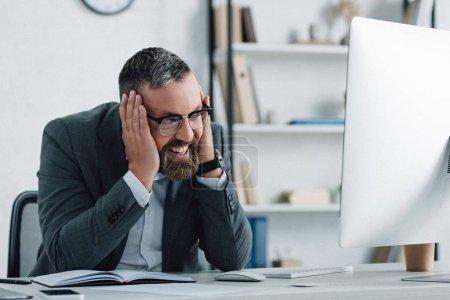 Photo pour Bel homme d'affaires en tenue formelle parlant sur smartphone et regardant l'ordinateur - image libre de droit