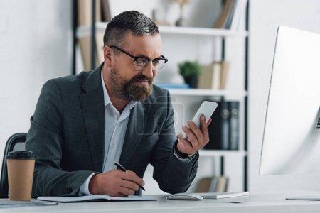 Photo pour Beau homme d'affaires dans l'usure formelle tenant le smartphone et le stylo - image libre de droit