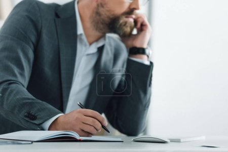 cropped view of businessman in formal wear talking on smartphone and holding pen