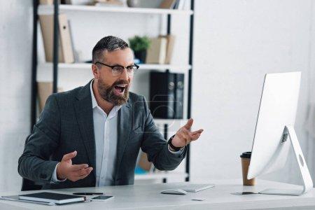 Photo pour Bel homme d'affaires dans l'usure formelle parlant dans le chat vidéo dans le bureau - image libre de droit