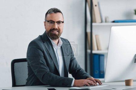 Foto de Guapo hombre de negocios en ropa formal sonriendo y mirando a la cámara - Imagen libre de derechos