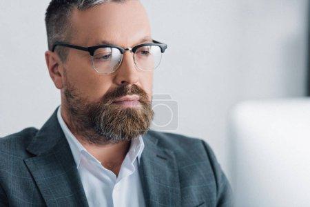 Foto de Enfoque selectivo de hombre de negocios guapo en el desgaste formal y gafas mirando hacia otro lado - Imagen libre de derechos