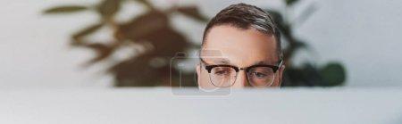 Photo pour Plan panoramique de l'homme dans des lunettes regardant loin dans le bureau - image libre de droit