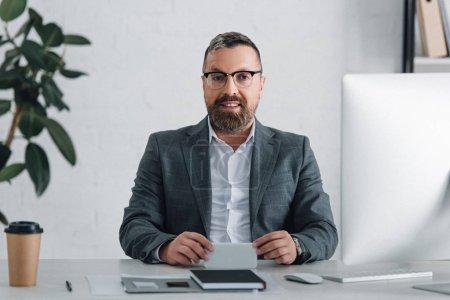 Photo pour Homme d'affaires beau dans l'usure formelle souriant et regardant l'appareil-photo - image libre de droit