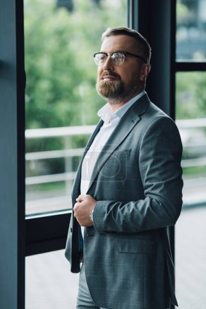 handsome businessman in formal wear and glasses looking away