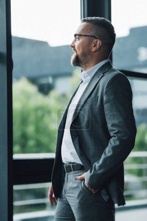 Photo pour Bel homme d'affaires en tenue formelle et lunettes détournant les yeux - image libre de droit