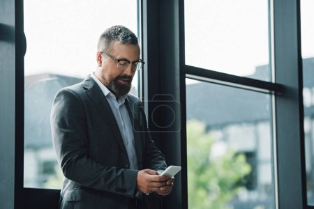 Photo for Handsome businessman in formal wear and glasses holding smartphone - Royalty Free Image