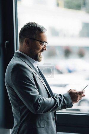 Photo pour Bel homme d'affaires en tenue formelle et lunettes tenant smartphone - image libre de droit