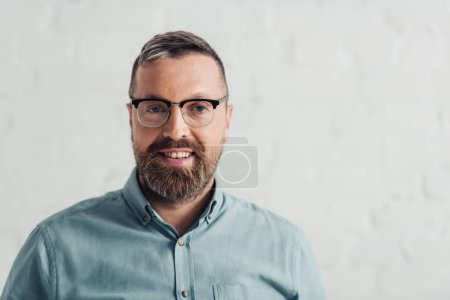 handsome businessman in shirt and glasses smiling and looking at camera