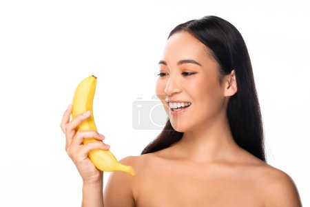Photo for Beautiful smiling naked asian woman looking at banana isolated on white - Royalty Free Image