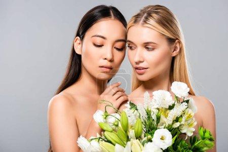 Photo pour Tendre belle blonde et asiatique brune femmes nues avec des fleurs isolées sur le gris - image libre de droit