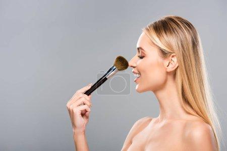 Photo pour Vue de côté de jeune femme nue de sourire avec le pinceau cosmétique d'isolement sur le gris - image libre de droit