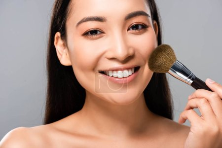 Photo for Smiling beautiful naked asian woman with cosmetic brush isolated on grey - Royalty Free Image