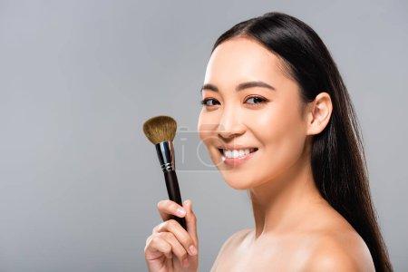 Photo pour Belle femme asiatique nue gaie avec le pinceau cosmétique d'isolement sur le gris - image libre de droit